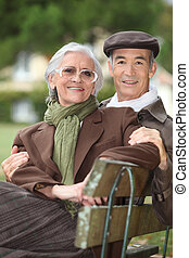 A mature couple on a bench.