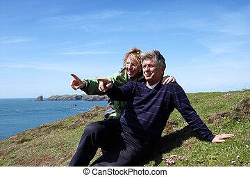 A mature couple sitting on the coastal path