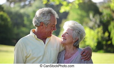 A mature couple standing in a park