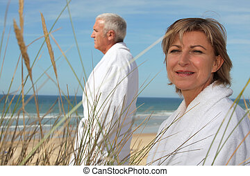 A mature couple wearing bathrobe at the beach.