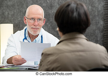 mature doctor with a patient in the office