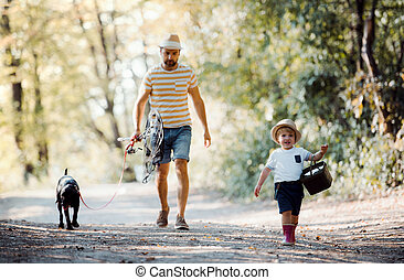 A mature father with a small toddler son and a dog going fishing.