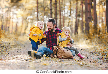 f32ee543491 A mature father with toddler children sitting on the ground in an autumn  forest.