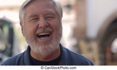 A mature healthy senior man laughing and smiling while outside