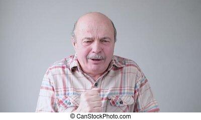 A mature hispanic man coughing because of pulmonary disease. Studio shot