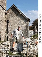 A mature man climbing over a wall