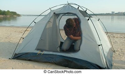 A mature man collects a tent on vacation outdoors near the sea