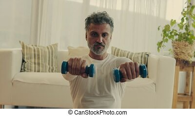 A mature man doing exercise at home.
