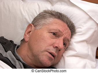A mature man laying in bed