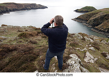 A mature man looking through binoculars