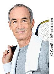 A mature man playing tennis.