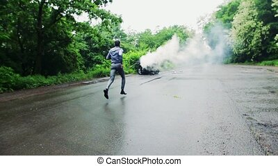 A mature man running towards the car in fire after an accident.