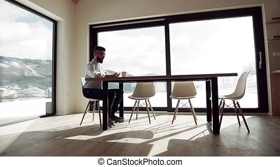 A mature man sitting at the table in new home, using tablet....