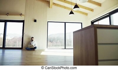 A mature man sitting on the floor in unfurnished new house, using laptop.