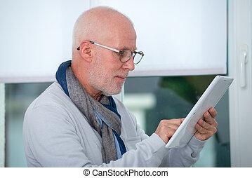 mature man using digital tablet at home