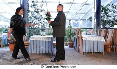 A Mature Man With A Bouquet Of Roses Meets A Woman At A Restaurant.