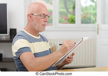 mature man with glasses taking notes