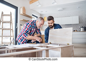 A mature man with his senior father assembling furniture, a new home concept.