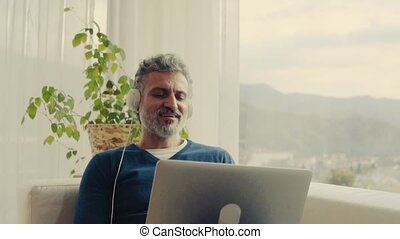A mature man with laptop and headphones at home.