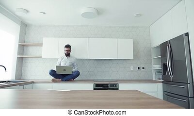 A mature man with laptop sitting on kitchen counter in new...