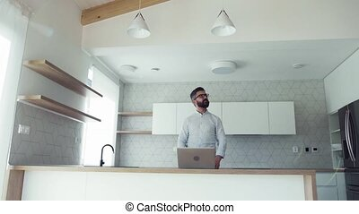 A mature man with laptop standing in kitchen in unfurnished...