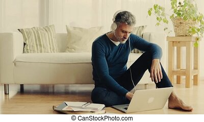 A mature man with laptop working at home.