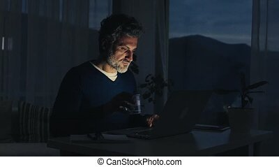 A mature man with laptop working in home office.