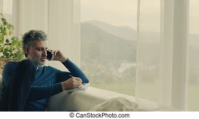 A mature man with smartphone at home. - A relaxed handsome...