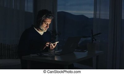 A mature man with smartphone working in home office.