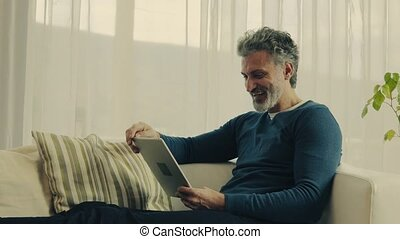 A mature man with tablet at home.