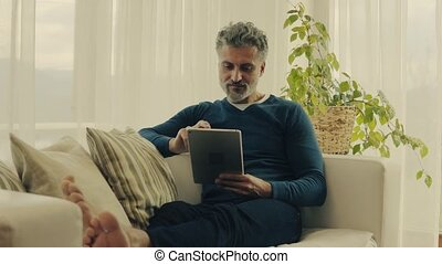 A mature man with tablet at home. - A relaxed handsome...