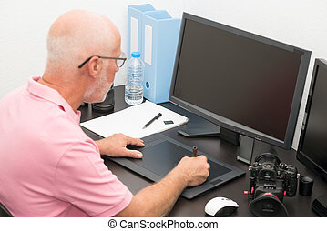 mature man working with graphics tablet in his office