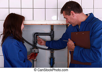 a mature plumber teaching to a female apprentice
