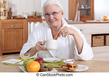 A mature woman having breakfast.
