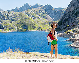 woman hiker in mountains with lake