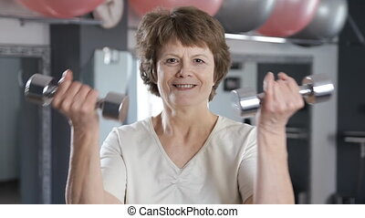 A mature woman lifting dumbbells, senior, fitness