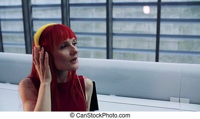 A mature woman with headphones in office, listening to music.