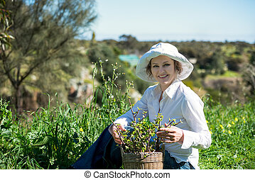 A mature woman  with plant in pot outdoors