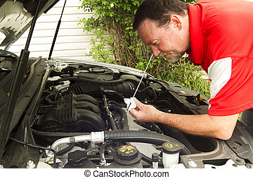 A Mechanic Checking The Oil In A Newer Car