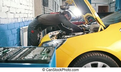 A mechanic checks the electrical in the hood of the car- repairing in engine compartment