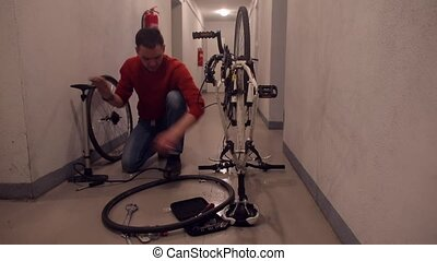 A mechanic inflates the rubber of a bicycle wheel to find a hole.