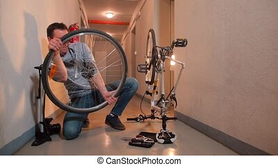 A mechanic inspects a broken bicycle wheel.