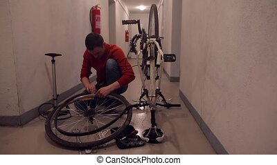 A mechanic makes manipulations with the rubber of a bicycle wheel.