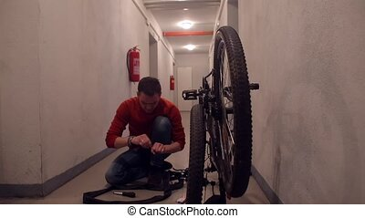 A mechanic makes manipulations with the rubber of a bicycle wheel in a garage.