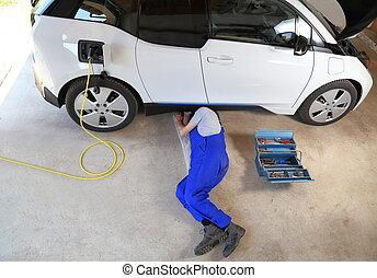 Mechanic repairing an electric driven car at garage