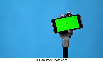 A mechanical hand holds a phone with a green screen. Gray cyborg hand holding a smartphone on a blue background. Chroma key.