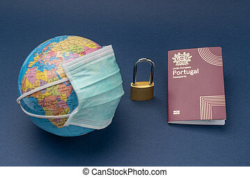 A medical mask is put on a globe of the globe with a Portuguese European passport and a padlock on a blue background.