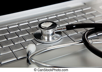 A medical stethoscope and an laptop computer - A medical...