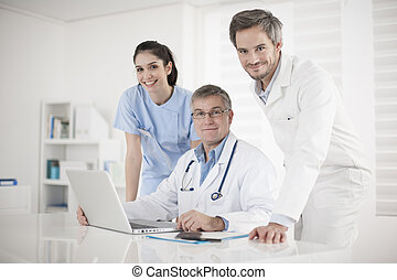 medical team discussing around a computer