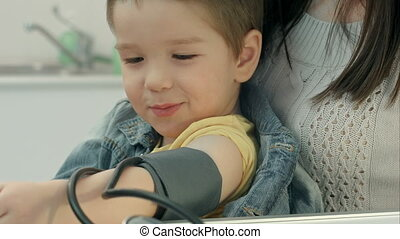 A medical worker taking a young boy's blood pressure